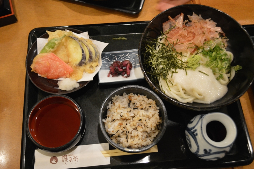 Cold udon with dried seaweed, katsuobushi, shallots and egg whites on the right, vegetable tempura on the left and rice and pickles in the middle