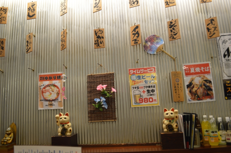 Walls of the okonomiyaki restaurant were decorated with Japanese script written on paper