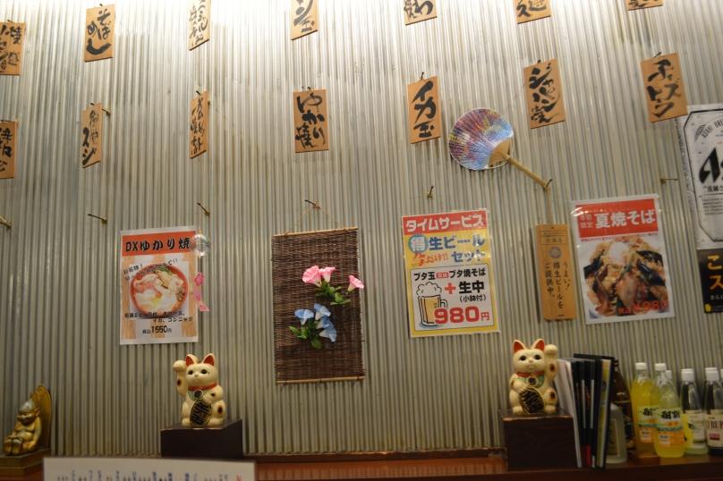 Walls of the okonomiyaki restaurant were decorated with Japanese script written on paper