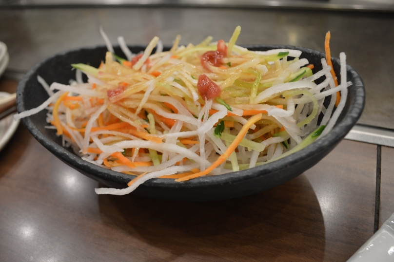 Salad of shredded carrots, radish and cucumber with dollops of tomato sauce